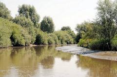 Lauf der Krückau bei niedrigem Wasser - an den Flussbiegungen entstehen Untiefen durch Ablagerungen.