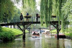 Brücke über eine Gracht in Friedrichstadt - grüne Zweigen von Weiden hängen tief über das Wasser.