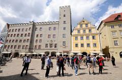 Haidplatz in Regensburg - Patrizierburg Goldenes Kreuz, erbaut 1250. Zinngekröntes Gebäude mit Turm. Touristen stehen in der Sonne auf dem Platz.