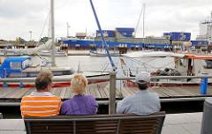 Blick über den Sportboothafen Brunsbüttel an der Schleuse - ein Containerschiff hat die Schleusenkammer verlassen und fährt in den Nord Ostsee Kanal ein.