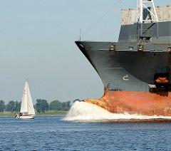 Bug eines kaum beladenen Frachters auf der Elbe in der Nähe der Einmündung der Stör in die Elbe - ein Segelboot fährt elbaufwärts und passiert das Frachtschiff.