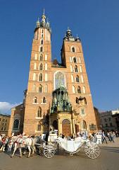 Türme der Marienkirche in Krakau / Kraków - die römisch katholische Basilika wurde vom 13. bis zum Beginn des 15. Jahrhundert, als klassisches Beispiel gotischer Architektur errichtet.  Eine weisse Kutsche mit weissen Pferden hält vor dem Eingang der
