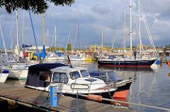 Segelboote und Motorboote liegen zum Teil nebeneinander in Päckchen.