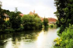 Ufer der Regnitz in Bamberg - Bäume und Sträucher am Wasser; im Hintergrund das Stadtarchiv und das Hotel Residenzschloss Bamberg.