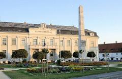 Architektur in Mosonmagyaróvár - Gerichtsgebäude und Stele mit Blumenrabatten.