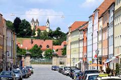 Häuserzeile mit farbigen Fassaden; Kirche der Hl. Dreifaltigkeit in Regensburg.