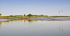 Landschaft Naturschutzgebiet Haseldorfer Binnenelbe - es ist Niedrigwasser, das Watt ist von Prielen durchzogen - Pricken markieren die schmale Fahrrinne.
