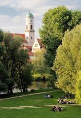 Park - Grünanlage in Regensburg; Menschen liegen unter Bäumen im Gras.