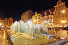 Springbrunnen am Abend auf dem Marktplatz von Wroclaw / Breslau in Polen; am Rande des Platzes historische und moderne Architektur.
