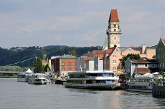 Ausflugsboote mit Touristen am Ufer der Donau von Passau - Rathausturm mit Uhr.