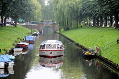 Fahrgastschiff mit geschlossenem Verdeck in einer Gracht von Friedrichstadt - Sportboote am Ufer des Kanals.