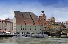 Fahrgastschiff mit Touristen auf der Donau - das Ausflugsschiff hat die Steinerne Brücke durchfahren - re. der Brückturm und am Donauufer das Salzstadl - erbaut 1620 zur Lagerung von Salz.