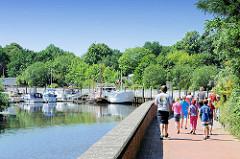 Promenade am Sportboothafen Bremervörde - Spaziergänger am Hafenrand - Sportboote im Hafen.
