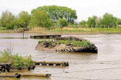 Holzwrack und Bohlen mit Wildkraut überwuchert bei Niedrigwasser im Watt des Störlochs, ein alter Arm der Stör an der Mündung.