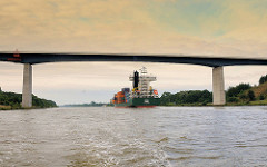 Brücke der A 23 über den Nord-Ostsee-Kanal; ein mit Containern beladenes Frachtschiff fährt unter der Brücke hindurch.