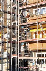 Baustelle - Baugerüst an einem mehrstöckigen Wohnhaus - Bauarbeiter auf dem Gerüst; Bilder aus der Stadt Mosonmagyaróvár, Ungarn.