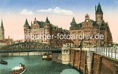 Blick auf die Wilhelminenbrücke - rechts führt eine steinerne Treppe zum Wasser. Ein Kran mit Handbetrieb steht an der Kaimauer vom Wilhelminenplatz. Am Kehrwiederfleet die Frontansichten der Speichergebäude A und J mti den neogotischen Gieb