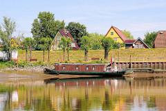 Blick von der Stör auf Wewelsfleet - ein Hausboot liegt bei Niedrigwasser im Schlick - hinter dem Deich Häuser des Dorfes.