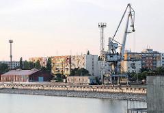Hafenanlagen - Hafenkräne in Komarno, Slowakei - im Hintergrund mehrstöckige Wohnblocks.