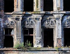 Alte Hausfassade mit Stucksäulen und Dekor - leerstehendes Wohngbäude.
