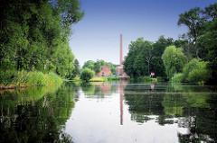 Alte Fabrikgebäude mit hohem Ziegelschornstein von Neu Kaliß spiegeln sich im Wasser des Elde Müritz Wasserwegs. Hohe Bäume und Schilf am Ufer des Wasserwegs.