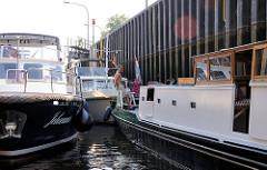 Sportboote schleusen in die Schleuse von Dömitz ein - die Motorboote liegen dicht beieinander in der Schleusenkammer.