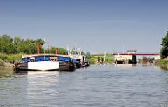 Schuten mit Schubschiff  an der Anlegestelle hinter dem Sperrwerk der Pinnau.