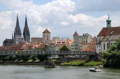 Panorama der Altstadt von Regensburg - lks. die Türme des St. Peter Doms, in der Bildmitte der Uhrturm des alten Rathauses; rechts die evangelisch lutherische Kirche St. Oswald. Ein Motorboot fährt auf der Donau beim eisernen Steg.