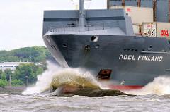 Frachtschiff OOCL Finland auf der Elbe in der Nähe der Einmündung der Stör in die Elbe. Hohe Gischt spritzt auf - der Containerfeeder pflügt sich durch die Wellen.