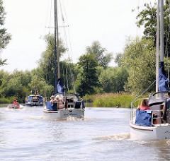 Sportboote in Fahrt auf der Krückau - Segelboote unter Motor und Motorboote.
