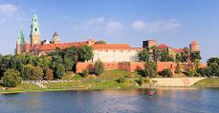 Blick über den Lauf der Weichsel - Wisla; Blick über den Fluss zur Wawel - Burgmauern und Türme der Kathedrale St. Stanislaus und Wenzel in Krakau / Kraków. Menschen in der Sonne in der Grünanlage des Weichselufers.