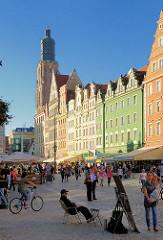 Markplatz mit historischen Fassaden in unterschiedlichen Farben am in Wroclaw, Breslau / Polen - im Hintergrund der Turm der St. Elisabethkirche.
