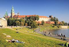 Sonniger Nachmittag in der Grünanlage am Ufer der Weichsel - Wisla. Die Menschen sitzen im Gras oder gehen an der Uferpromenade spazieren. Im Hintergrund der Wawel; Burg - Residenzschloss und Türme der Kathedrale in Krakau / Kraków.