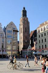 Blick über den Marktplatz von Wroclaw / Beslau; Touristen und Spaziergänger in der Sonne - im Hinergrund historische Architektur / Hausfassaden und der Kirchturm der St. Elisabeth Kirche - gotischer Kirchenbau, Backstein Anfang des 14. Jahrhunderts -