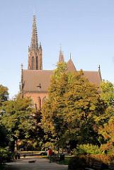 Die St. Michaeliskirche in Wroclaw, Brelau zwischen Bäumen - Parkbesucher gehen in der Sonne spazieren.