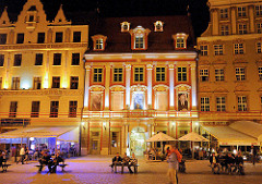Abend - Nachtaufnahme, beleuchtete Hausfassaden historischer Häuser im polnischen Wraclaw, Breslau. Touristen sitzen im Freien an Tischen unter Markisen oder auf Bänken auf dem Marktplatz.
