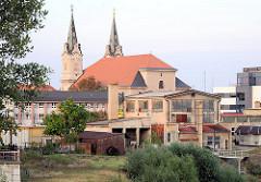 Gewerbegebäude, Industriearchitektur in Komarno, Slowakai - im Hintergrund die Kirchtürme der barocken Kirche Sv. Ondreja / St. Andreas