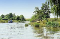 Landschaft an den Ufern der Krückau - Schafe weiden im dichten Gras, ein Sportboot fährt flussabwärts.
