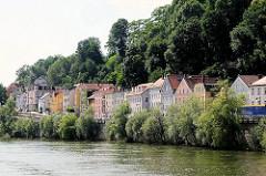 Mehrstöckige Wohnhäuser mit bunter Fassade am Ufer der Donau in Passau.
