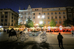 Abend in Krakau - Pferdekutsche; Restaurants unter Sonnenschirmen auf dem Hauptmarkt in Krakau.