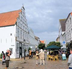 Touristenstädtchen Friedrichstadt - Backsteinrenaissance, Fussgängerpassage mit Touristen; Café auf dem Gehweg.