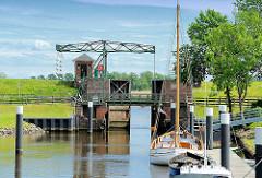 Blick über die Schleusenkammer zur Klappbrücke und dahinter die Stör - Boote liegen am Anleger.