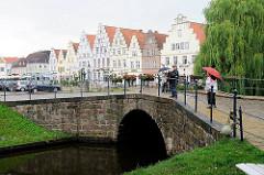 Blick über eine Gracht zur historischen Architektur am Marktplatz von Friedrichstadt.