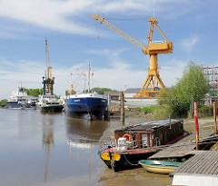 Werft in Wewelsfleth - Schiffe liegen am Werftkai; im Vordergrund ist ein Hausboot bei Niedrigwasser trockengefallen.