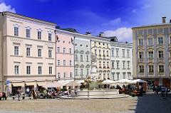 Historische Architektur Passau - Residenzplatz - der Platz ist nach der Alten Bischöftlichen Residenz benannt - Strassencafe mit Sonnenschirmen. In der Mitte steht der Wittelsbacher Brunnen; er wurde 1903 zur Erinnerung an das 100-jährige Jubiläum.