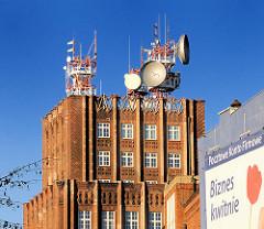 Expressionistisches Postscheckamt Breslau, Wroclaw - Ziegelgebäude, Backsteinfassade - Satellitenschüsseln und Sendeanlagen auf dem Dach.