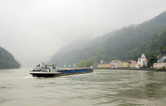 Ein rumänisches Binnenschiff fährt auf der Donau flussaufwärts - die bewaldeten Berge links und rechts des Donauufers sind von Wolken / Dunst eingehüllt.