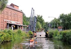 """Die Klappbrücke vor der Schleuse """"Findenwirunshier"""" ist hochgeklappt - ein Sportboot fährt in die Schleusenkammer ein - zwei Kanus warten."""