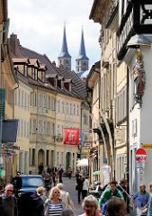 Fussgänger - Touristen in einer Strasse in Bamberg -  im Hintergrund zwei Türme des Kaiserdoms von Bamberg.