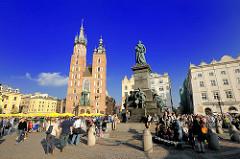 Hauptmarktplatz von Krakau  - Wohnhäuser und Marienkirche - Adam-Mickiewicz-Denkmal. Touristen schlendern in der Sonne über den Platz.